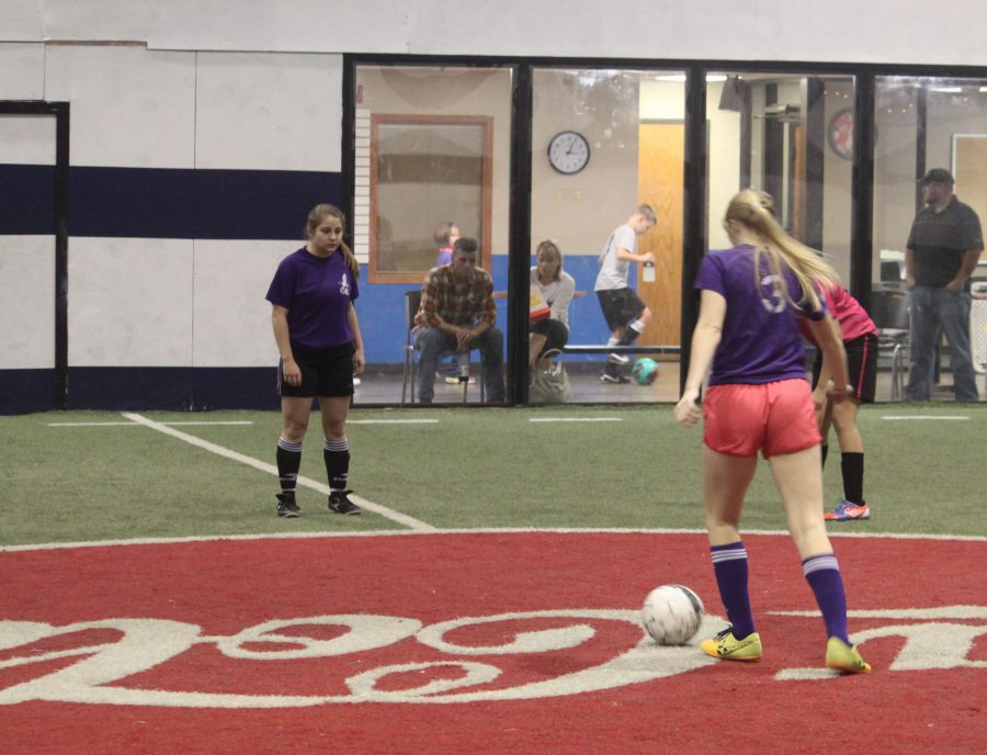 Maegan Holland (12) dribbles the ball during indoor soccer game. PHOTO BY NEWSPAPER STAFF