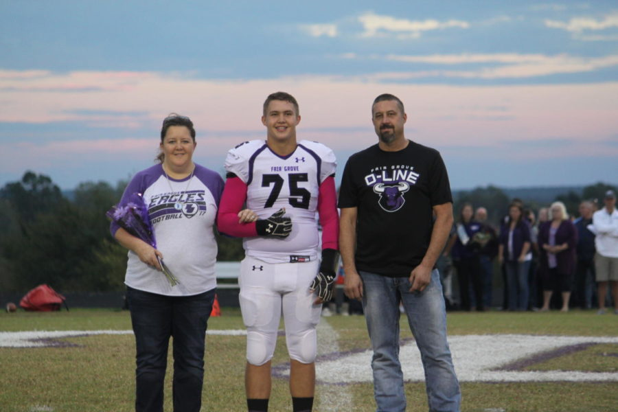 Senior Colton Dame walks out during halftime with his parents.