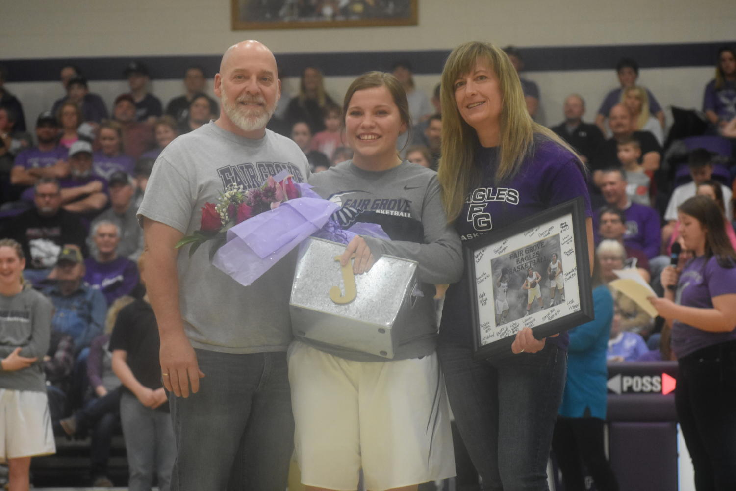 Senior basketball player Jordan Coddington with her parents during senior night.