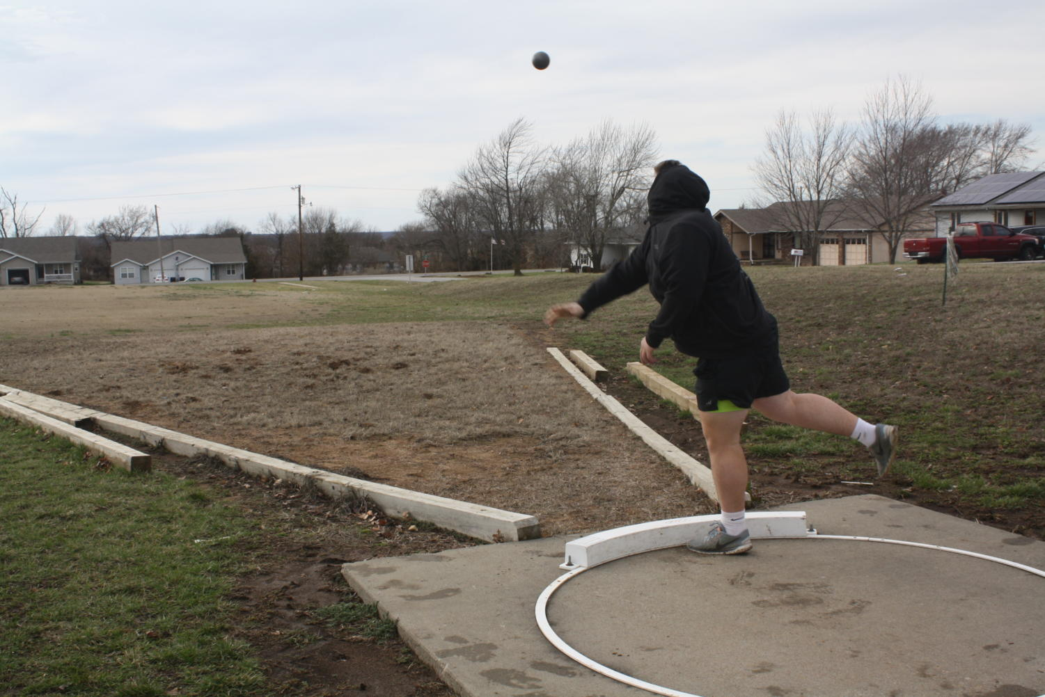 Junior Cody Gunder practices shot put.