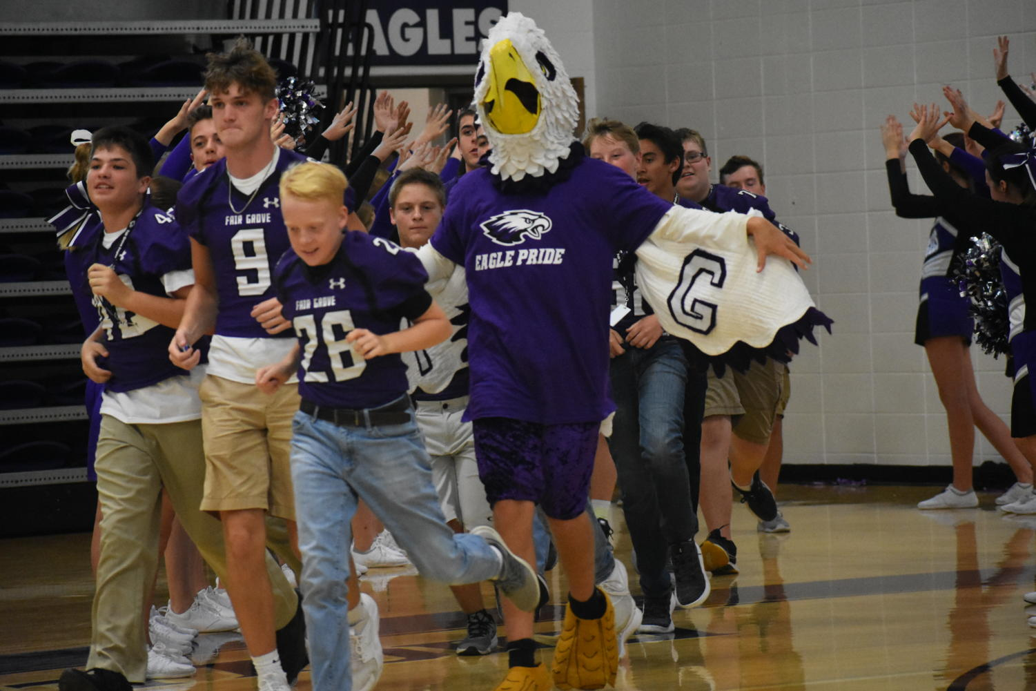 The Eagle runs out with members of the football team at the pep assembly