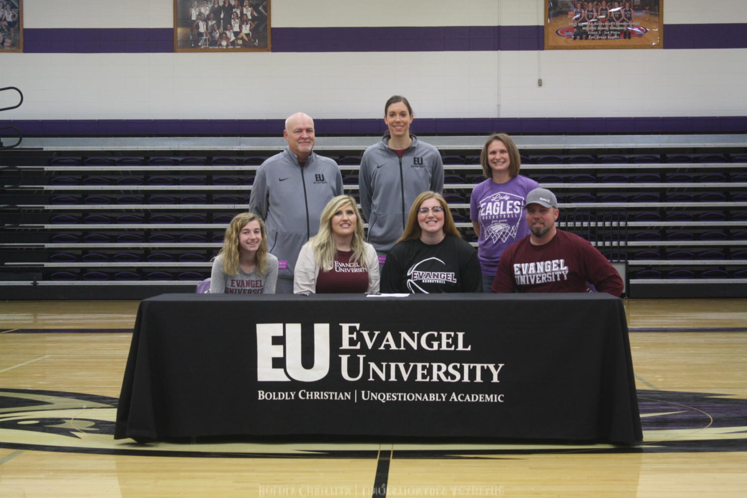 Harley Maxwell (12) poses with her family and Evangel basketball coaches