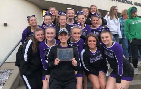 The cheer squad poses wit their plaque