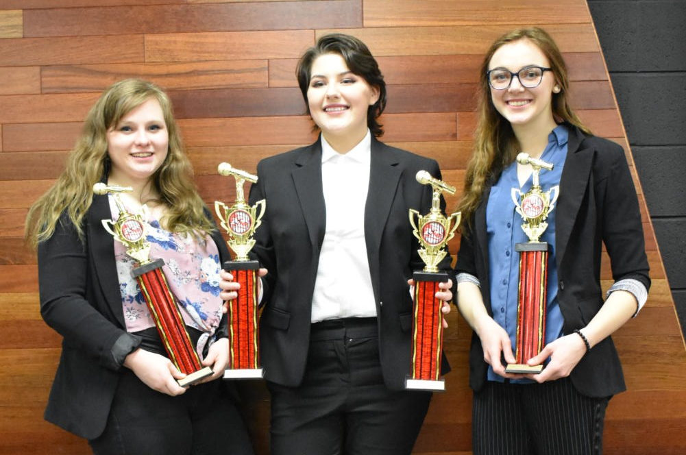 Emma Hackett (12) , Georgia Whalley (11) , and Kayla Hodges (12) pose with their trophies