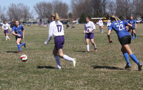 Gracie Rowden [12] dribbles the ball down the field.