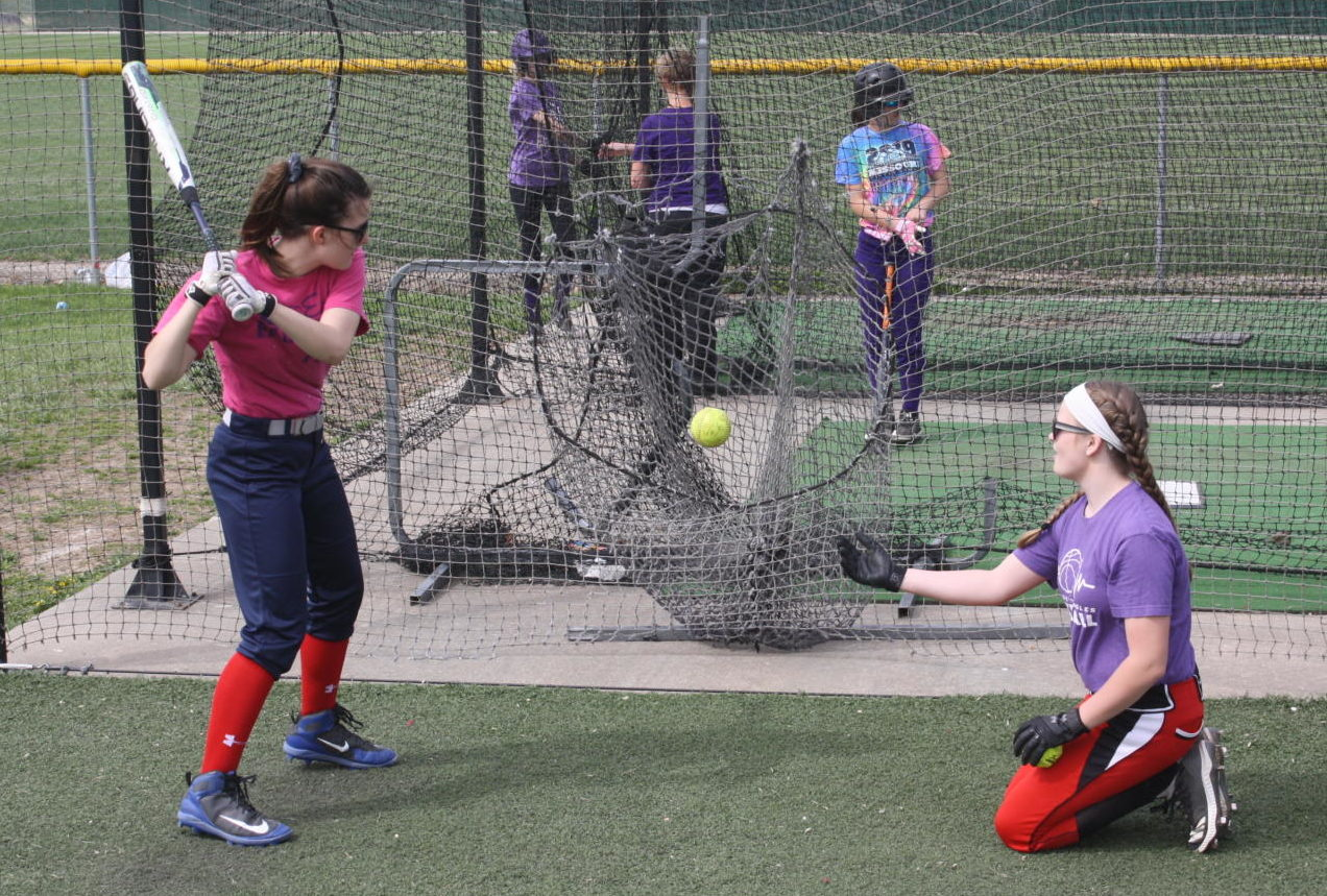 The MS Softball team practices in the batting cage.