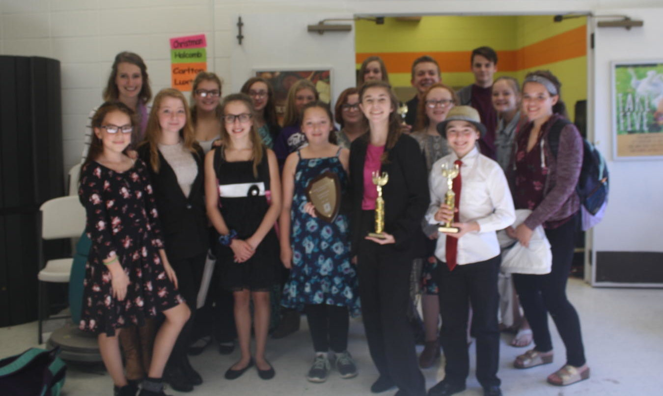 Middle School Speech and Debate team poses with their  trophies.