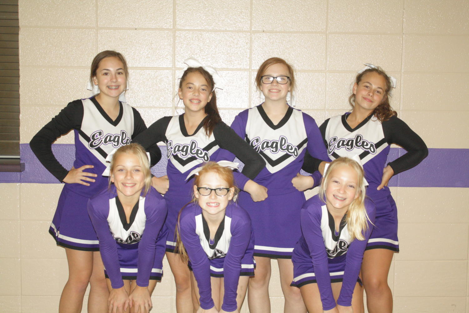 Middle school cheerleaders posing after a night of cheering