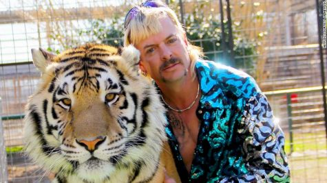 Joe Exotic posing with a pet tiger.