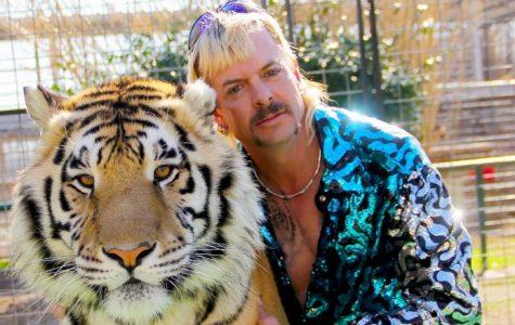 Joe Exotic posing with a pet tiger.