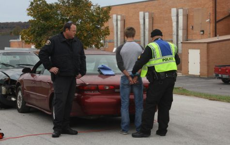 Former Fair Grove PD Officers Derek Zentner and Brian Way (from left to right) reenact a car crash scene in a presentation for Fair Grove students.