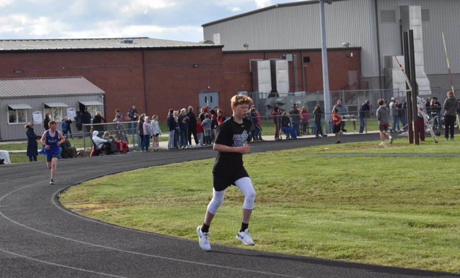 An athlete running in their event at a middle school track meet.