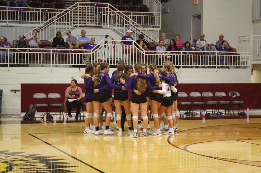 Fair Grove varsity Volleyball Team joining together after scoring a point.